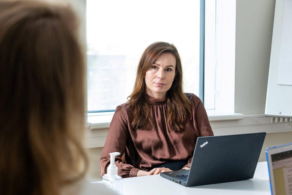Helepruunide juustega naine istumas arvuti taga ja vaatamas kaugusesse.