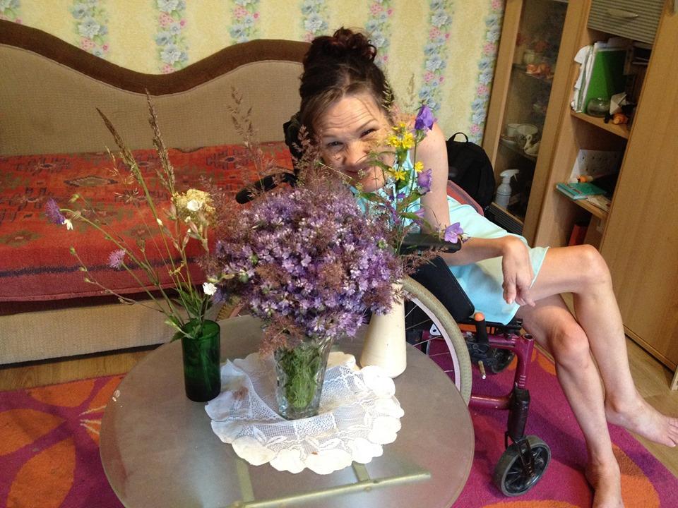 Naeratav ja ratastoolis istuv tumepruunide juustega naine lillakate lillede taamal enda kodus.