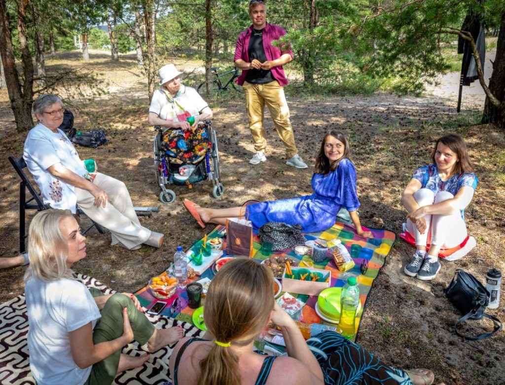 Mändidega parkmetsas toimuval Helpificu piknikul on näha rõõmsaid inimesi. Osad istuvad maapinnal tekil, erivajadusega 2 vanemat naist ratastoolis ja toolil, üks noormees roosa jaki ja beežide pükstega seisab püsti ja vaatab kaugusesse.
