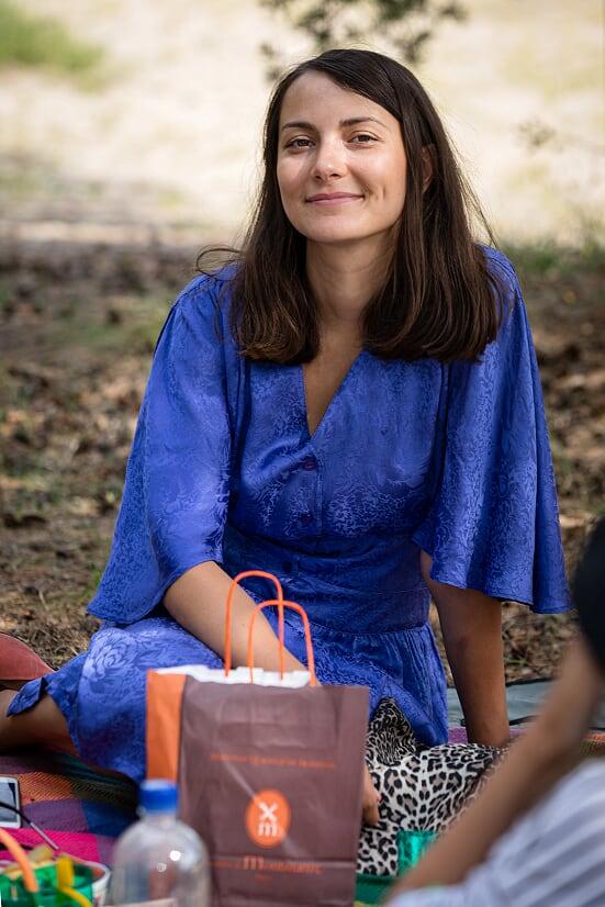 Parkmetsas piknikutekil istuv sinises kleidis ja tumepruunide juustega naine naeratab kaamerasse.