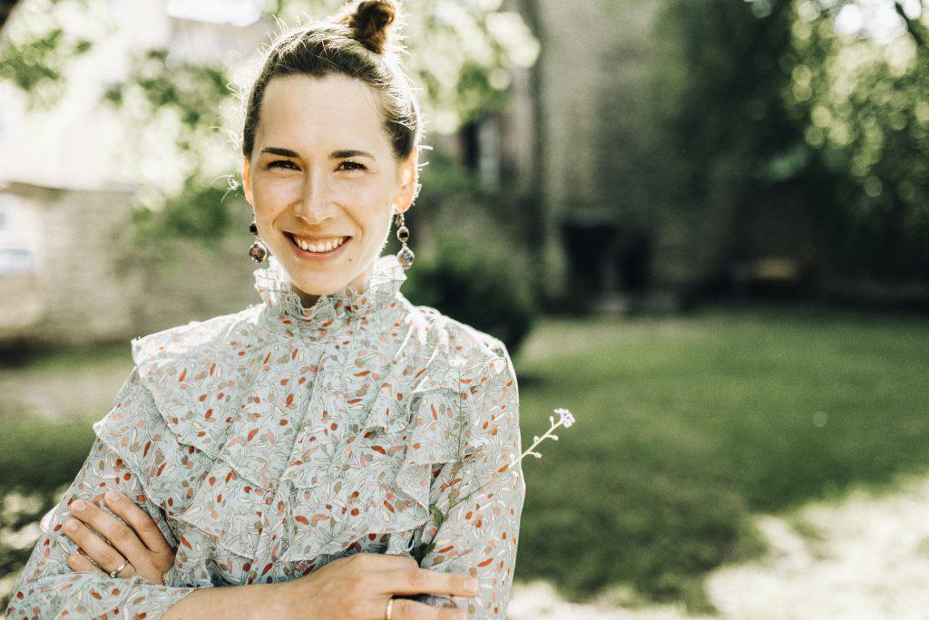 Helesinise mustrilise triiksärgi ja krunnikeeratud tumepruunide juustega naeratav naine looduses.